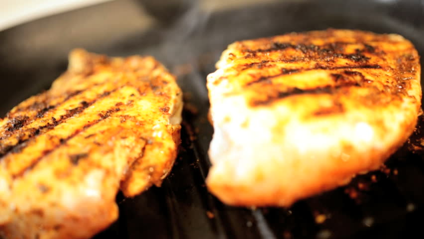 Organic white meat chicken breast meat grilling on a griddle pan slow motion view
