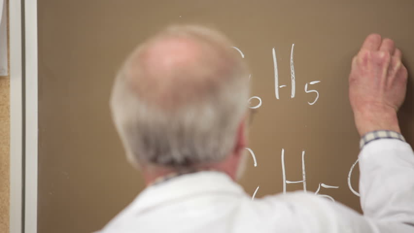 A professor writes an equation on the board with his back turned to the class