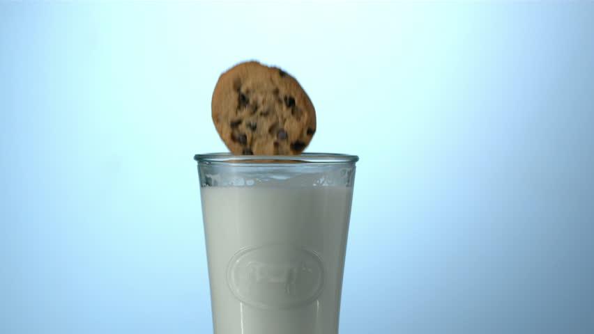 Cookie splashing into glass of milk, slow motion