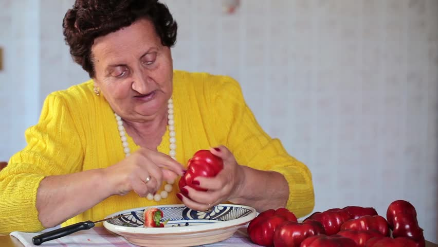 Footage of senior woman removing core and seeds of tomato peppers.