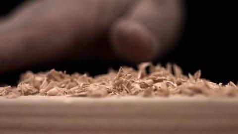 Hand brusing off wood shavings, slow motion