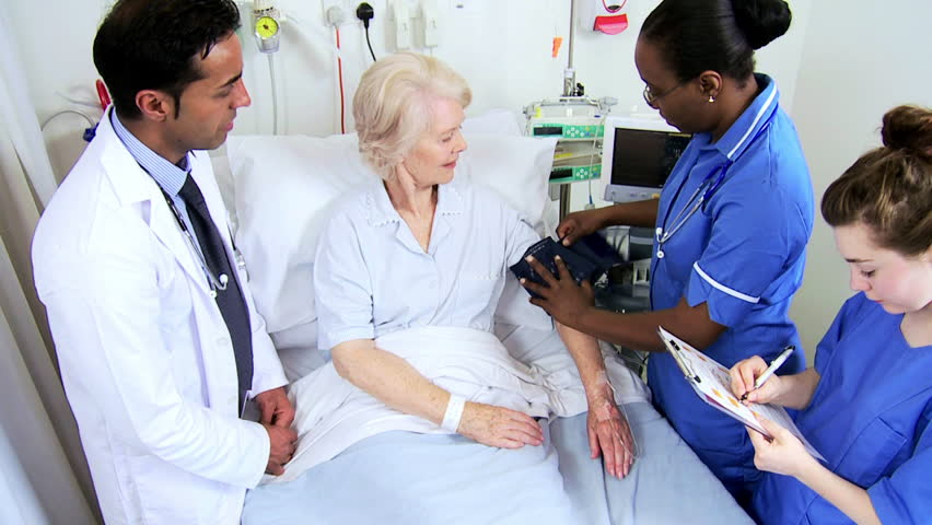 Older Caucasian female patient having blood pressure taken by a caring team of health care professionals #4761413