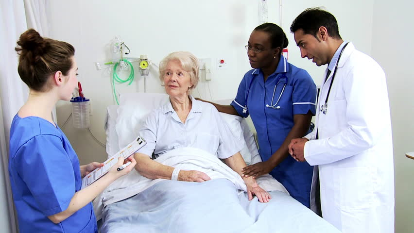 Medical specialist and attending nurses discuss diagnosis with a hospital patient #4762373