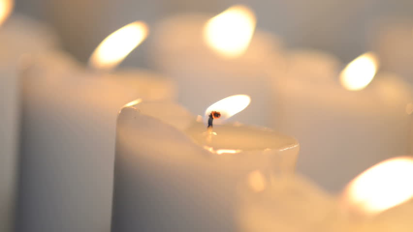 Close Shot Of A White Candle Burning With Bright Candle Light. Few Candles