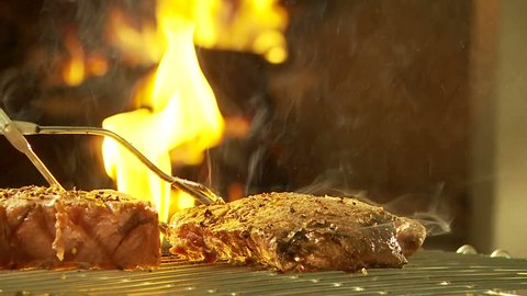 Slow motion of sirloin steak turned on flaming grid. Slow dolley movement