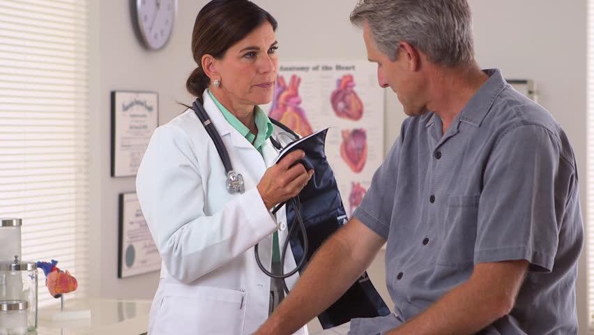 Woman doctor checking elderly man's blood pressure