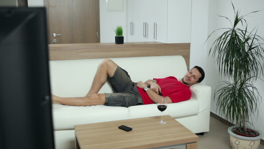 Man lying on couch at home and watching TV. High definition video. | Shutterstock HD Video #4805303