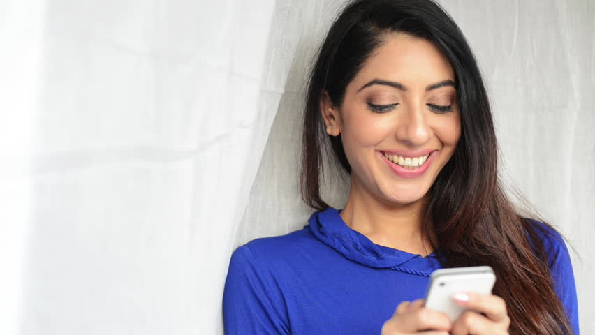 Locked-on shot of a smiling woman using a mobile phone