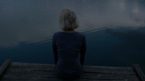 Woman sitting on a pier and staring at water (shot day for night). High definition video.