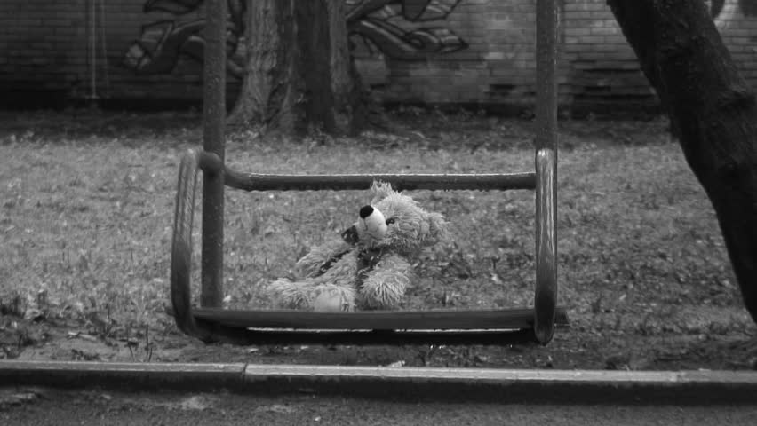 Forgotten Teddy bear on a swing under rain. Deep depression theme. Black and white.