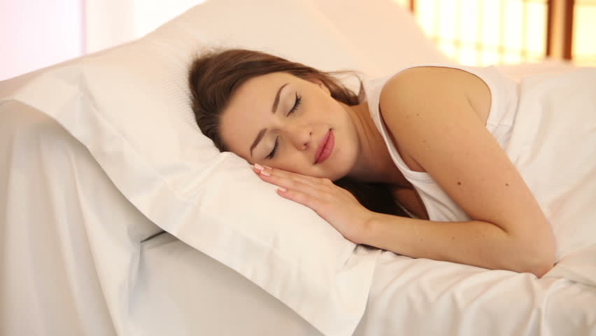 Cute girl sleeping in bed waking up and smiling at camera. Panning camera