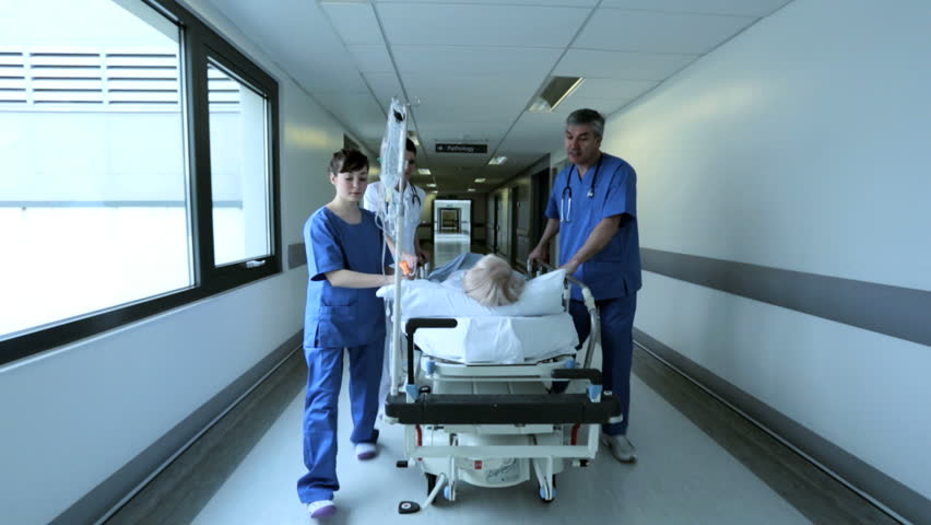 Caring medical staff moving patient in hospital bed to clinical treatment center in hospital