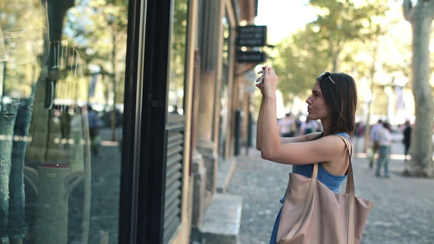 Woman taking photo of clothes on shop window in the city
