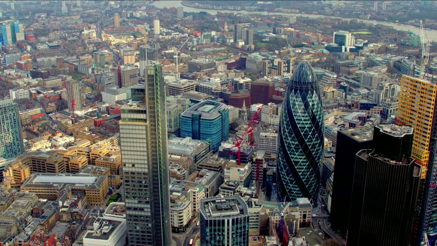 Dramatic aerial shot of the City of London financial district skyline. Features the Gherkin / 30 St Mary Axe building - shot then reveals Tower Bridge. #4835516