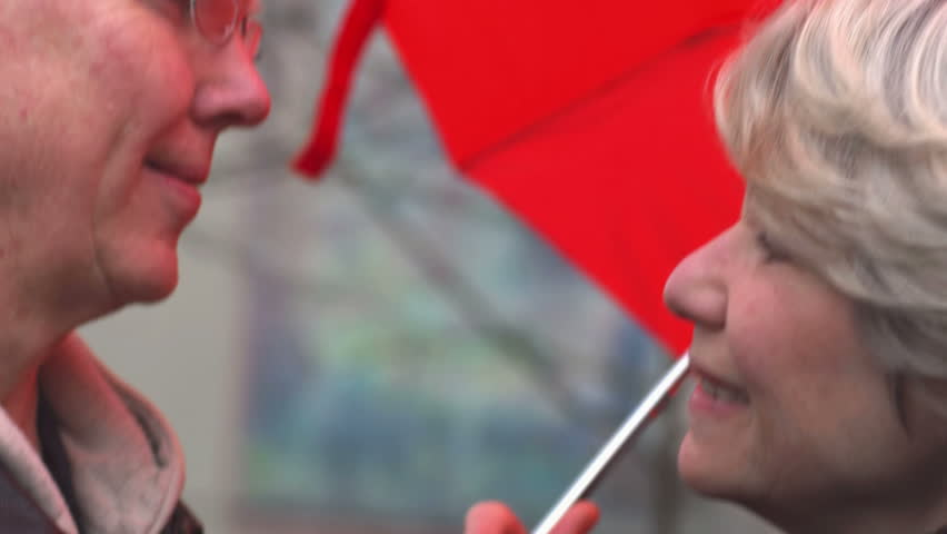 An older man and woman stand under a red umbrella and kiss