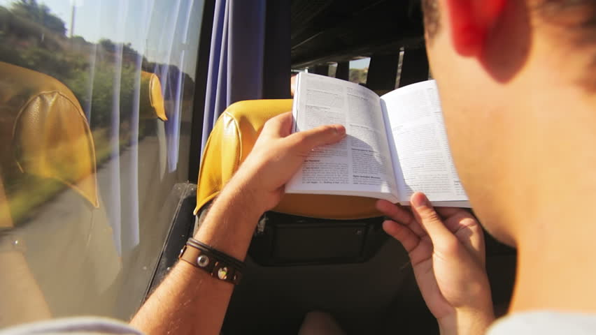 Over the shoulder shot of a man reading a book on the bus