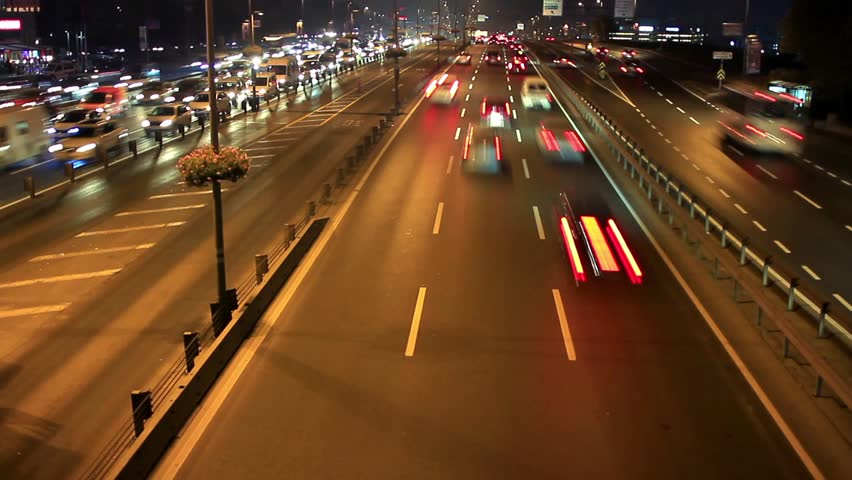 Highway through city at night time lapse. Busy light trail traffic on a freeway