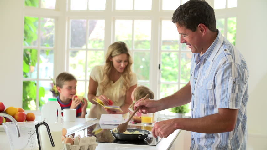 Father makes breakfast for family as mother reads to young children in kitchen