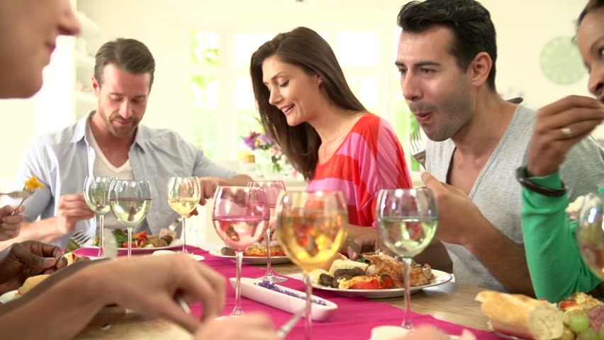 Young adult friends laughing and eating around a table together