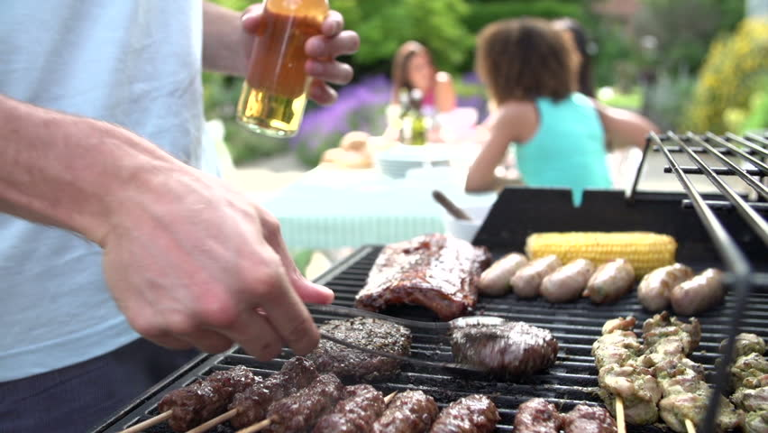 Close up of man food grilling on barbecue while women sit at backyard table and relax