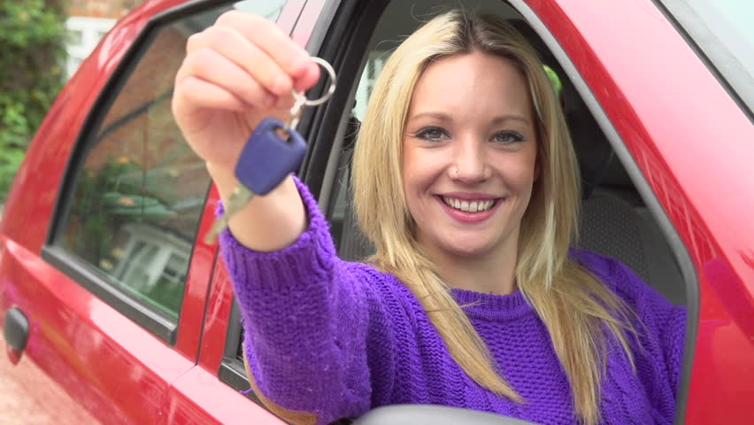 Happy teenage girl sits in car and dangles car keys out window in slow motion