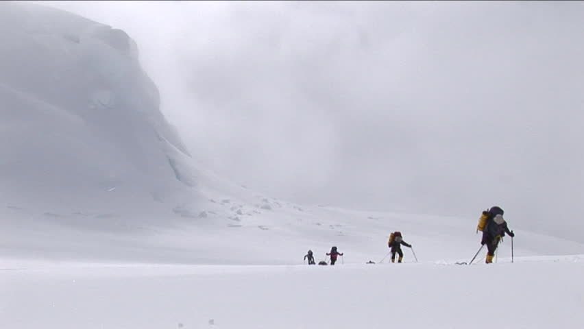 Climbers ascending with snow coming down