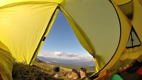 View of the mountain valley with lake through the window in the camping tent