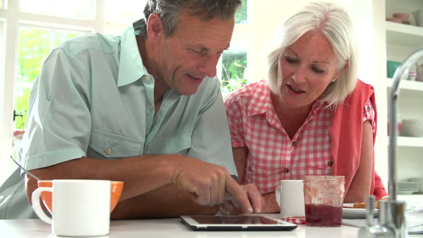 Older couple talking and using wireless tablet together during breakfast