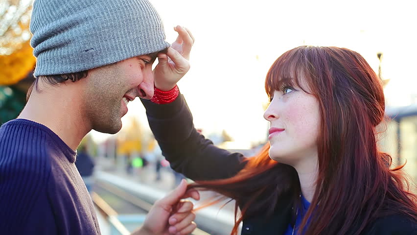 A young couple kiss and flirt while they wait on a train platform for the next arrival, close up