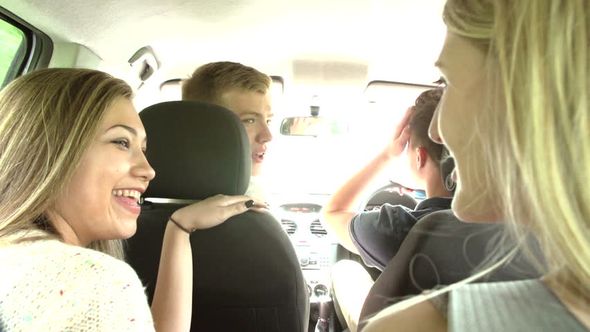 Four teenage friends driving on a rural road having fun