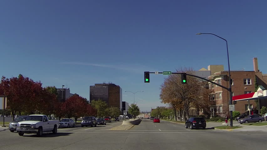 SALT LAKE CITY UTAH OCT 2013: Urban center traffic and downtown business. LDS Business College POV HD. Driving point of view vehicle through busy streets. Business, hotels, office apartment buildings.