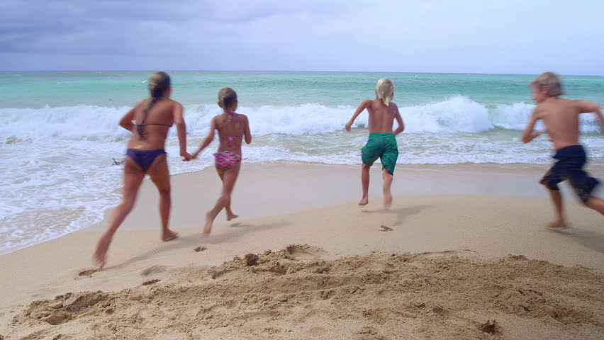 Four Kids Run Away From The Camera And Into Ocean