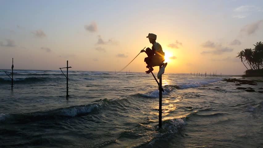 KOGGALA, SRI LANKA - OCT 7: Sri Lanka stilt fisherman at sunset on October 7, 2013 in Koggala, Sri Lanka