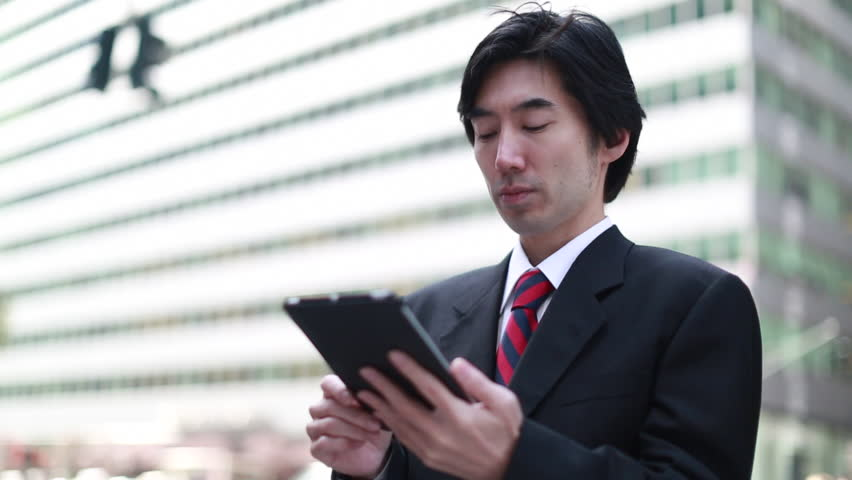 Asian businessman in New York City Park Avenue street using iPad tablet pc