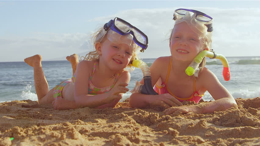 Two adorable little girls lie on the beach and smile for the camera while wearing their snorkel gear. Medium shot.