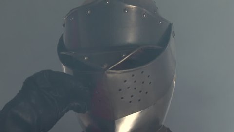 Knight walking in fog and lifts mask