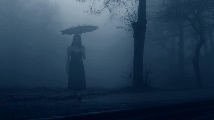 Woman in black dress walking through the mist