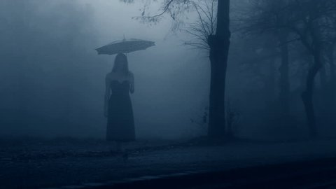 Woman in black dress walking through the mist