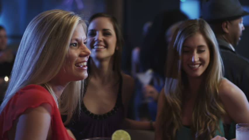 Three girls sit at a bar having a fun time with the bartender