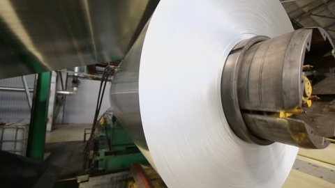 Aluminum sheet uncoils from roll on special machines of rolling mill in workshop at metallurgical plant