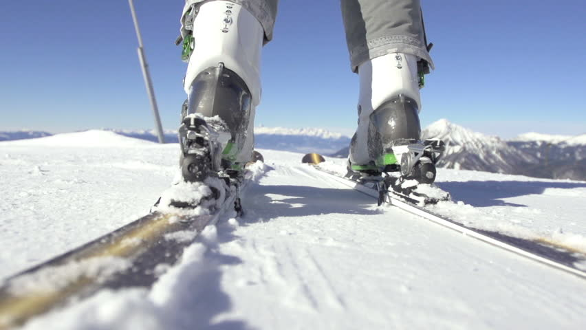 Slow Motion Close Shot Of Ski Boots Being Attached To Carving Skis.