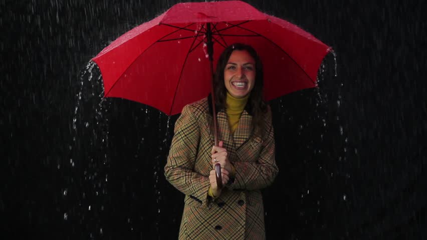 Enthusiastic woman standing in rain - Stock Image - F014