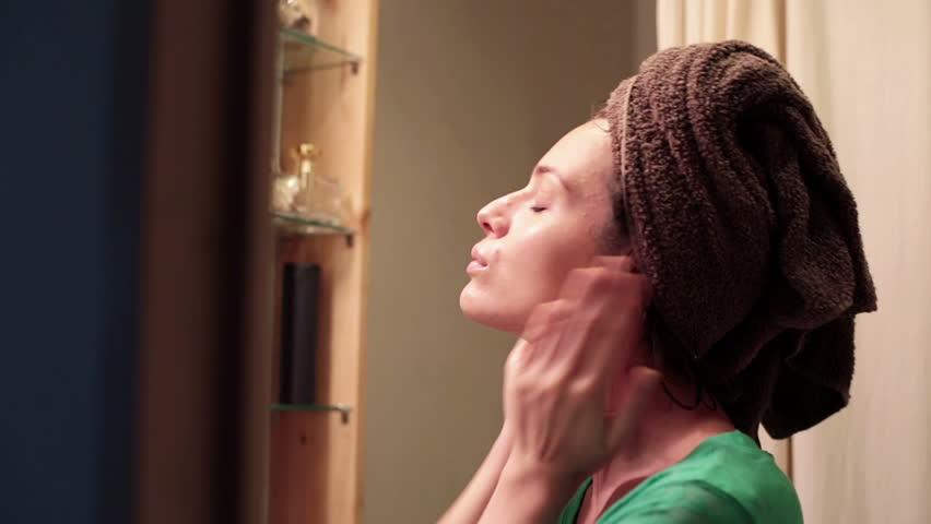 Attractive woman applying moisturiser creme on her face in bathroom