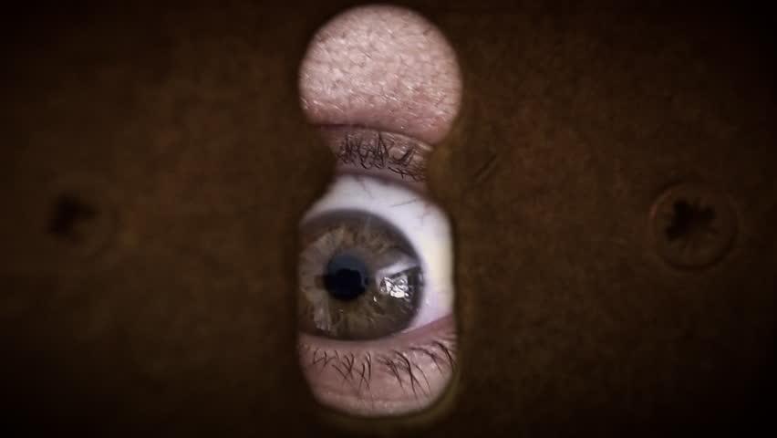 Macro shot of the eye of a zombie. Disturbing, scary, spooky shot. Seen through a keyhole.