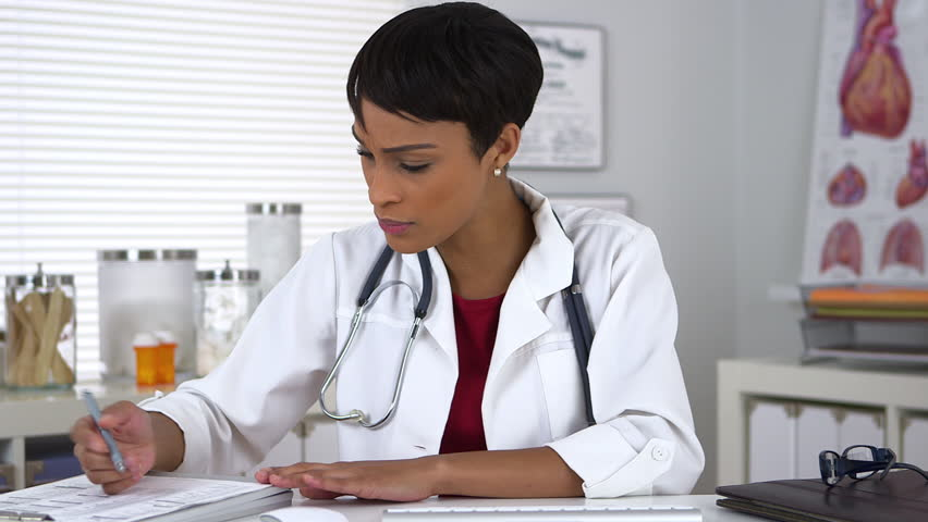 Black doctor talking to the camera and taking notes