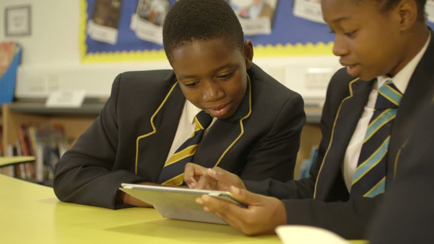 MS Schoolboy and schoolgirl using tablet in library