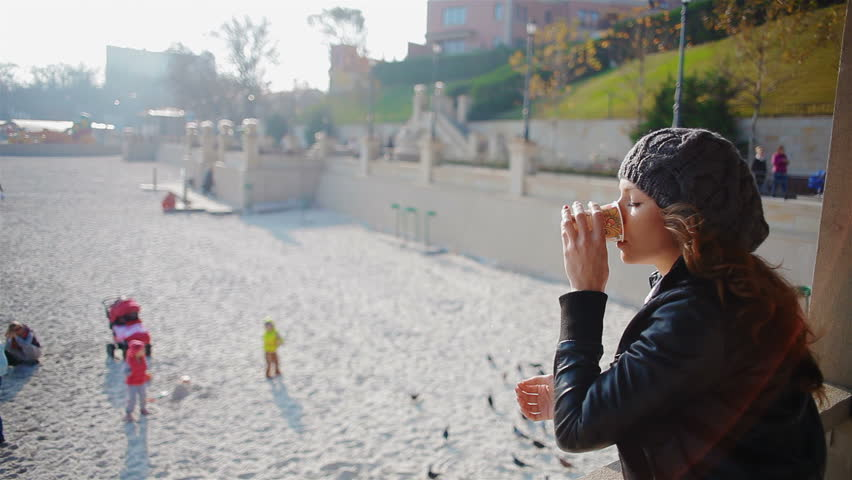 Young, attractive woman drinking coffee outside. The girl looks at the beach and enjoying a fall day | Shutterstock HD Video #5105513