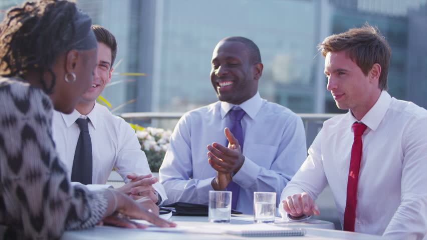 Happy mixed ethnicity business team or successful  group of friends, chatting and laughing as they sit together on an open air city roof terrace. In slow motion. | Shutterstock HD Video #5109383