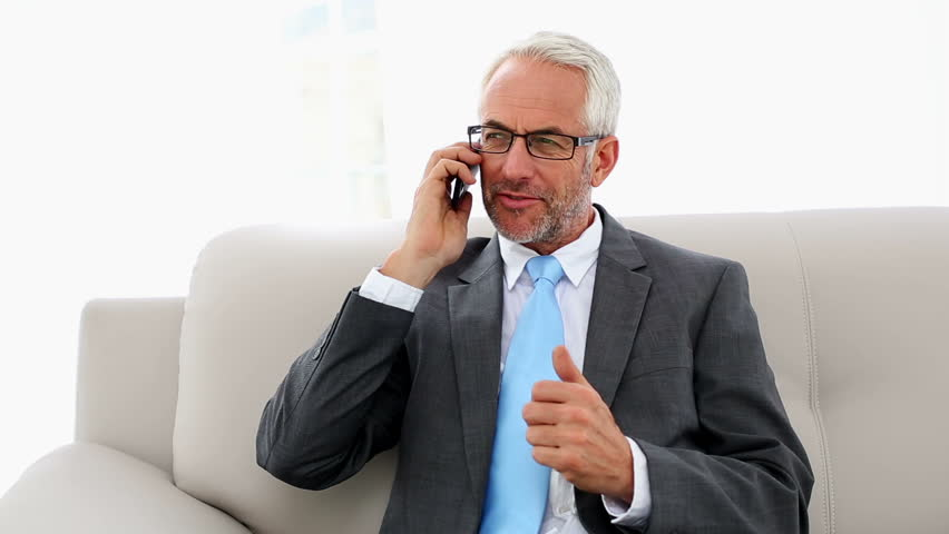 Businessman talking on the phone on the couch in office staff room