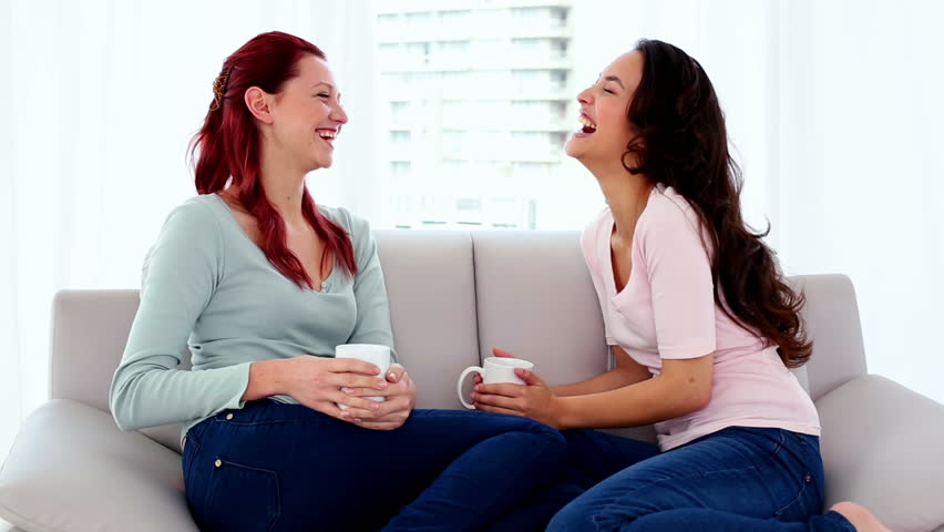 Beautiful amused women sitting on couch while having a conversation in bright living room
